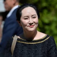 Huawei Technologies Chief Financial Officer Meng Wanzhou smiles as she leaves her home to attend a court hearing in Vancouver in May.  | REUTERS