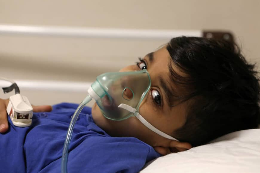 Parham, a 7-year-old Iranian boy suspected to be infected with the coronavirus disease, is treated at Mofid children's hospital, in Tehran, on July 8. Global coronavirus cases exceeded 12 million on Wednesday, according to a Reuters tally. | A. HEIDARI / VIA REUTERS