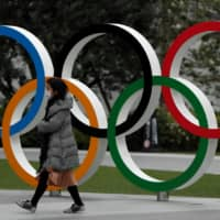 A woman wearing a protective face mask walks past the Olympic rings in front of the Japan Olympics Museum in Tokyo on March 30. | REUTERS