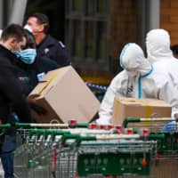 Members of the Melbourne Fire Brigade prepare to take food parcels to residents in a locked down public housing estate in Melbourne on Thursday as the city re-enters a city wide lockdown after a fresh outbreak of the COVID-19 coronavirus. | AFP-JIJI