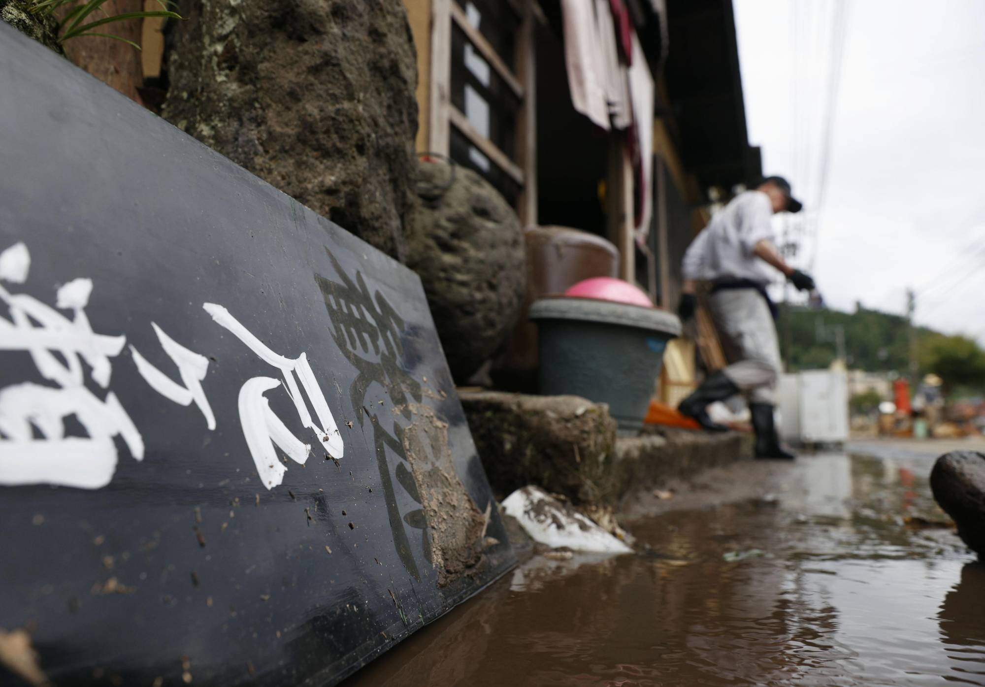 A signboard saying 'welcome' at a hot-spring inn in Hita, Oita Prefecture, lies on the ground in the mud after torrential rain devastated the popular hot-spring resort of Amagase. | KYODO