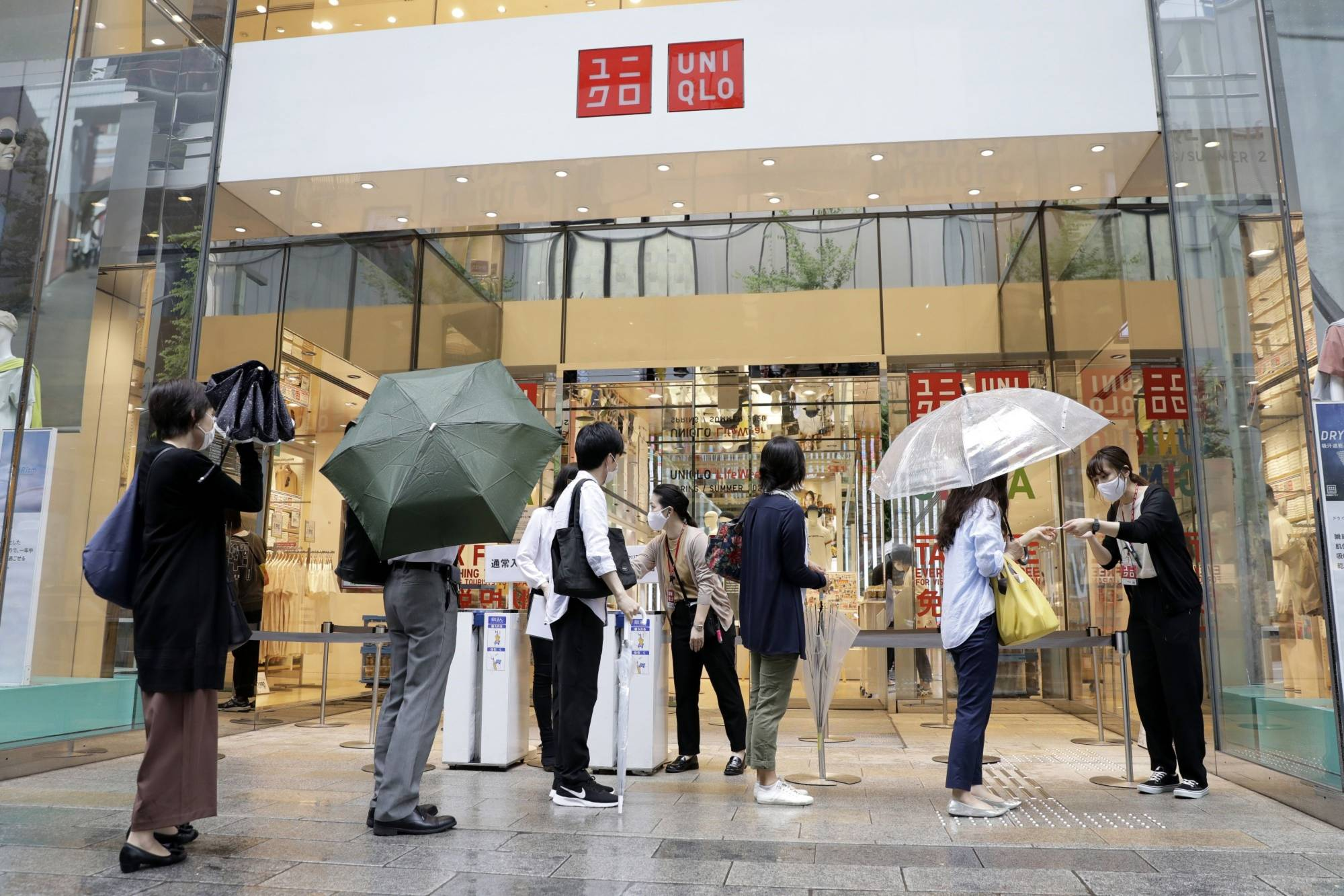 Customers queue to collect tickets allowing them to purchase Uniqlo AIRism masks at a Uniqlo store, operated by Fast Retailing Co., in Tokyo last month.   BLOOMBERG