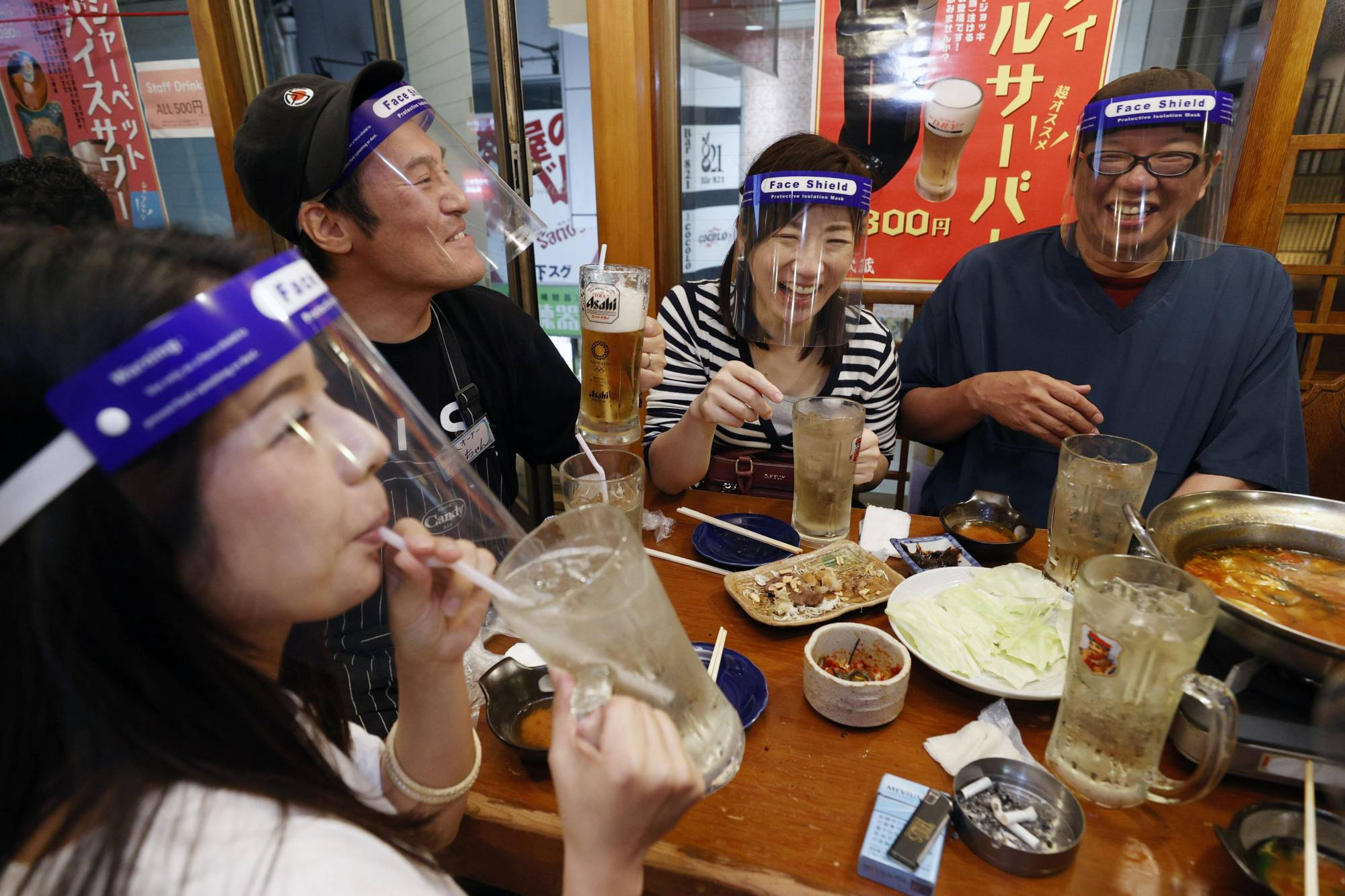 Sneeze guards: Customers wear face shields at a restaurant in Osaka. The term for the plastic masks is being used more often in Japanese conversation. | KYODO