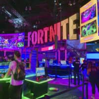 People try out video games at the Epic Games booth at Electronics Entertainment Expo (E3) in Los Angeles in June last year. | KYODO