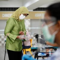 The gloves come on: Virus-hit Singapore heads to the polls