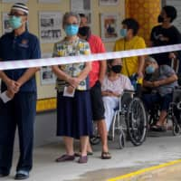 Voters wait to cast their ballots during the general election in Singapore on Friday.    AFP-JIJI