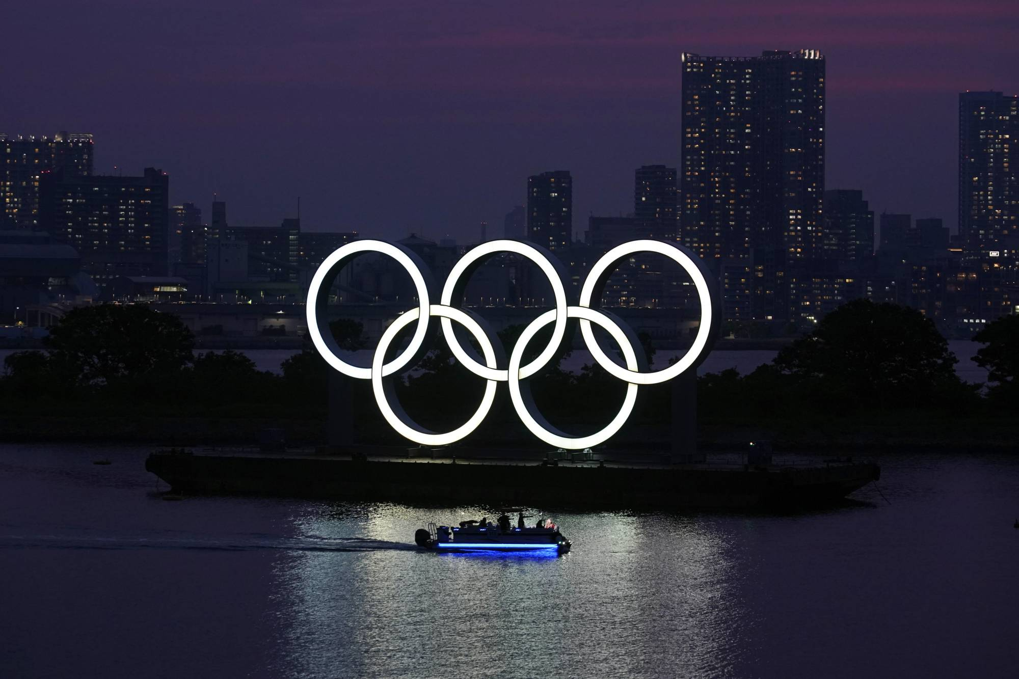 The Olympic rings float in the water at sunset in Tokyo's Odaiba waterfront district. | AP