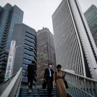 The skyscrapers of Shinjuku tower over passersby on the stairs in Tokyo on June 24 as the coronavirus pandemic causes companies to question the future of the office. | REUTERS