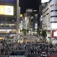 Pedestrians cross an intersection at night in the Tokyo's Shibuya Ward on Friday. | BLOOMBERG