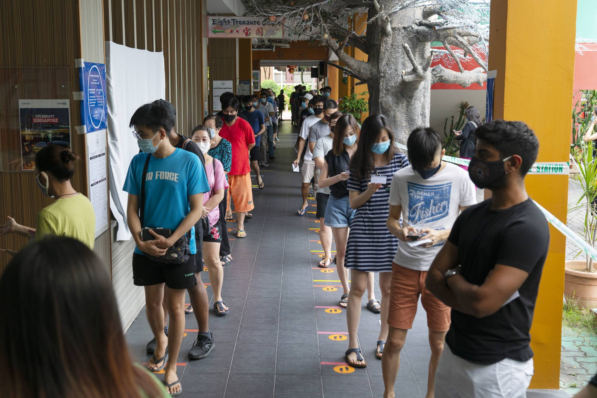 Voters observe social distancing measures while waiting in line at a polling station in Singapore on Friday.   BLOOMBERG