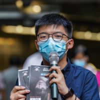 Joshua Wong speaks outside a subway station on Saturday. Wong and other prominent activists cut ties with political groups after the law's enactment, an apparent bid to avoid implicating each other. | BLOOMBERG