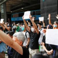 Supporters raise blank white paper to avoid slogans banned under Hong Kong's new national security law on July 3.  | REUTERS