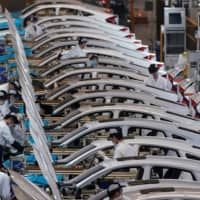 Employees work on a production line in April inside a Dongfeng Honda factory after lockdown measures in Wuhan were eased.  | REUTERS