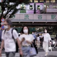 People wearing face masks walk outside JR Shibuya Station on Friday. Tokyo confirmed 206 new cases of COVID-19 on Saturday.   BLOOMBERG