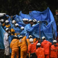 Rescue workers hold up a blue sheet as they recover a victim's body during a search for people still missing in Fukuhama, Kumamoto Prefecture, on Saturday after torrential rains spurred floods and landslides devastated the region earlier in the week. | AFP-JIJI