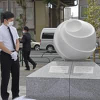 Takuya Matsunaga stands next to a monument unveiled Saturday in Tokyo to his wife and young daughter, who were killed by a car in April 2019 driven by an 87-year-old former senior bureaucrat. | KYODO