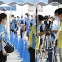 Staff check fans' temperatures before they enter Todoroki Stadium on Saturday. | KYODO