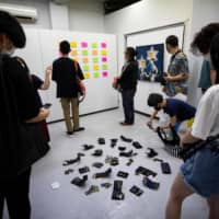 Visitors look at artworks in Same Gallery during the opening ceremony of the Stealable Art Exhibition in Tokyo on Thursday, hours before the gallery let people steal the art. | AFP-JIJI