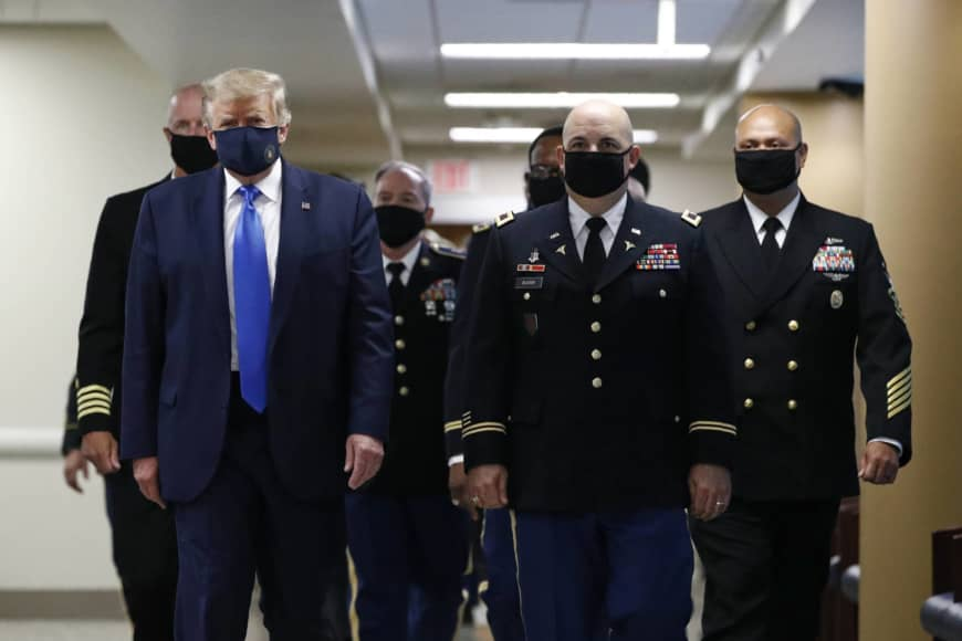 U.S. President Donald Trump wears a face mask as he walks down a hallway during a visit to Walter Reed National Military Medical Center in Bethesda, Maryland, on Saturday.   AP