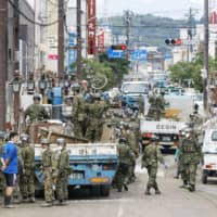 Residents and Self-Defense Forces personnel work on clearing up the streets in the disaster-hit city of Hitoyoshi, Kumamoto Prefecture, on Sunday. | KYODO