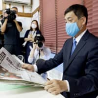 New Kagoshima Gov. Koichi Shiota, a former industry ministry bureaucrat, looks at a newspaper Monday morning in the city of Kagoshima following his victory in the gubernatorial election the previous day. | KYODO