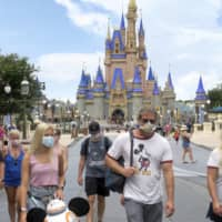 Guests wear masks as required to attend the official reopening day of the Magic Kingdom at Walt Disney World in Lake Buena Vista, Florida, on Saturday. | ORLANDO SENTINEL / VIA AP