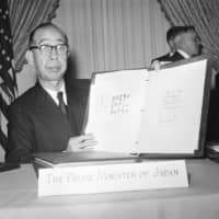 Prime Minister Nobusuke Kishi displays the United States-Japan security treaty after the signing ceremony at the White House on Jan. 9, 1960. The man who stabbed him on July 14 that year said he was unhappy with Kishi's handling of the ratification process and wanted to punish him. | AP