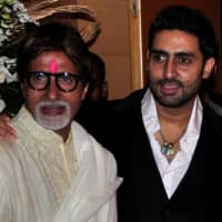 Bollywood actors Amitabh Bachchan (left) and his son, Abhishek, pose for a picture during a party in Mumbai in February 2010. | REUTERS