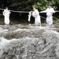 Shinto priests dressed in traditional costume take part in an event to exchange a shimenawa sacred rope that spans the river above Nachi Falls in Nachikatsuura, Wakayama Prefecture, on Monday.   KYODO