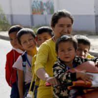 A Uighur woman and children sit on a motor-tricycle in Hotan, in western China's Xinjiang region, in September 2018. China on Monday slapped retaliatory sanctions on three senior Republican lawmakers and a U.S. envoy in a deepening row over Beijing's treatment of Uighurs in the region. | AP