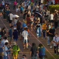 People line up to vote in Hong Kong on Sunday in an unofficial primary for pro-democracy candidates ahead of legislative elections in September. Hong Kong reported 41 local coronavirus cases on Monday, another record high as the resurgence of infection looks set to grow into the city's biggest wave yet.   AP