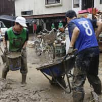 High school students have been drafted in as volunteers to help clear mud in Hitoyoshi, Kumamoto Prefecture, where a number of hot spring operators have opened their doors for free to help affected workers and residents. | KYODO