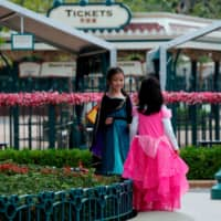 Children play outside the Hong Kong Disneyland after it closed amid the coronavirus outbreak in January.  | REUTERS