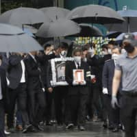 A man holds a portrait of late Seoul Mayor Park Won-soon as mourners leave Seoul City Hall after his official funeral on Monday.  | AP