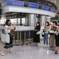 A woman waves as she is seen off by her friends at Narita Airport on June 25, before boarding a chartered flight to Vietnam's Van Done. | KYODO