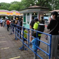 Visitors line up at the entrance of Toshimaen amusement park in Tokyo on Monday. | AFP-JIJI
