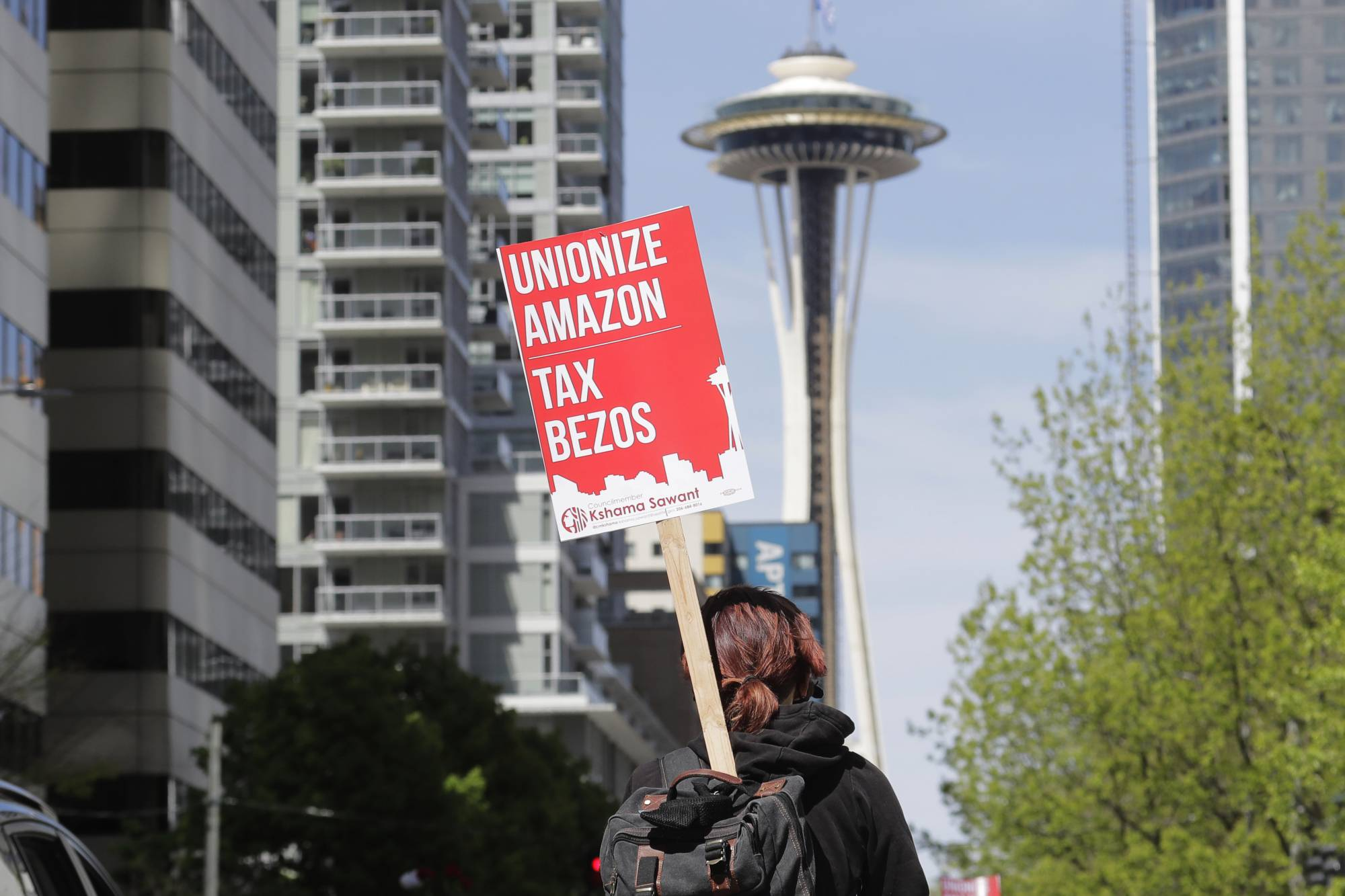 A protester carries a sign that reads 'Unionize Amazon Tax Bezos' during a protest in downtown Seattle on May 1.  | AP