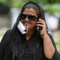 A teacher holds the facemask with her mouth as she speaks on a mobile phone during the COVID-19 coronavirus pandemic, in Hyderabad, India, on July 9. Indian police are having a field day handing out fines to people who do not wear a mask during the coronavirus pandemic. | AFP-JIJI