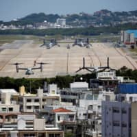 MV-22 Osprey tilt-rotor aircraft are seen at U.S. Marine Corps Air Station Futenma in Ginowan, Okinawa Prefecture, in March 2018. Defense Minister Taro Kono on Tuesday drew attention to 'several problems' with the U.S. military's prevention measures after coronavirus infections at five of its bases in the prefecture surged to a total of nearly 100 cases. | REUTERS
