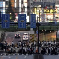Pedestrians cross a road at dusk on Friday in Tokyo's Shinjuku Ward, where a cluster of coronavirus infections has been detected. | BLOOMBERG