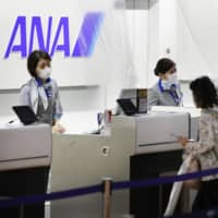 Passengers check in at an All Nippon Airways check-in counter at Tokyo's Haneda Airport on July 1.   KYODO
