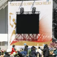 Workers take down displays marking the start of the torch relay for the 2020 Tokyo Olympics on March 25 at J-Village in Fukushima Prefecture. | KYODO