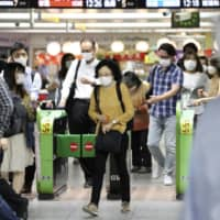 Passengers wearing face masks to protect against the spread of the new coronavirus walk through the gates at Yokohama Station on Tuesday. The health ministry said the same day that it has discovered neutralizing antibodies in samples collected from eight people who tested positive for the virus. | AP