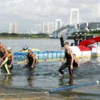 Swimmers come out of the water after the marathon swimming event of a test competition for the Tokyo Olympics in August in 2019 at Tokyo's Odaiba Marine Park. | KYODO