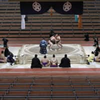 Yokozuna Hakuho (left) fights Kakuryu on the final day of the Spring Grand Sumo Tournament on March 22 at an empty Edion Arena Osaka. | KYODO