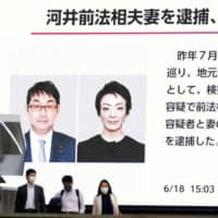 A screen in Tokyo's Akihabara district shows a news report that Katsuyuki Kawai and his wife, Anri, were arrested on June 18 on suspicion of vote-buying. | KYODO