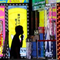 A man wearing a face mask walks past a signboard for a bar in the Kabukicho entertainment district of Shinjuku Ward, Tokyo, on Tuesday night. | REUTERS