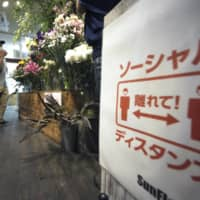 A sign reminding customers to keep a safe distance from each other to avoid the spread of the novel coronavirus is seen at a florist on Monday in Tokyo. | AP