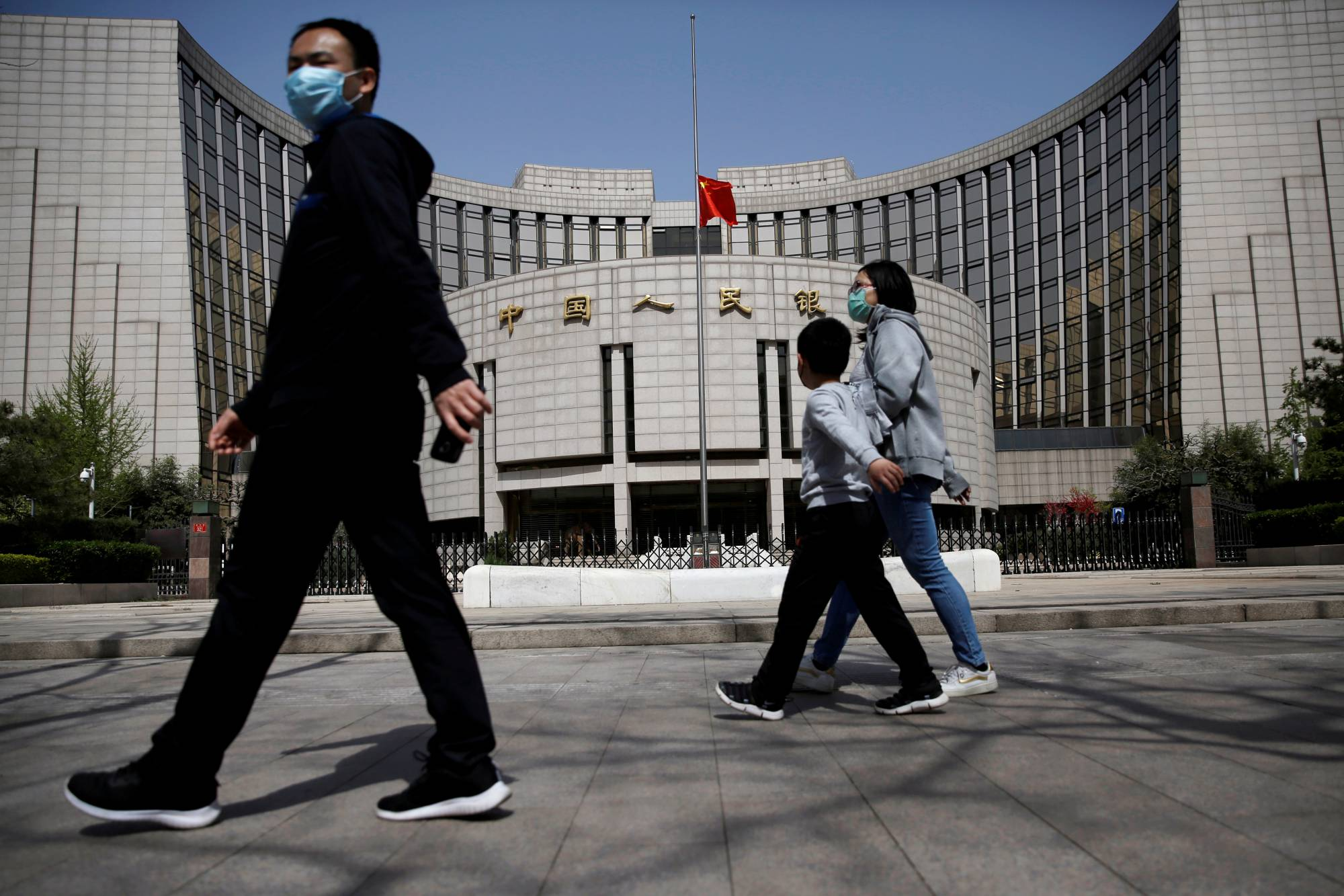 People walk past the headquarters of the People's Bank of China in early April. Just since the past month, worried savers in China have descended on three banks to withdraw funds amid rumors of cash shortages that were later dismissed as false.   | REUTERS