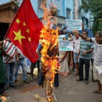 Demonstrators shout slogans as they burn an effigy depicting Chinese President Xi Jinping in Kolkata, India, following a deadly clash on the border between the two countries. | REUTERS